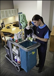 A Service Master Clean female janitorial cleaning service team member emptying trash into a cart.